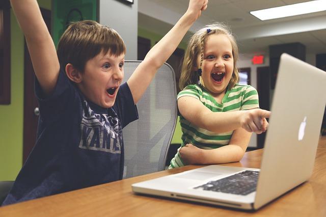 パソコンを見て喜ぶ子供