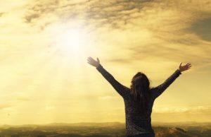 朝日を見つめ手を上げる人