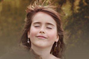 目を閉じてほほ笑む少女