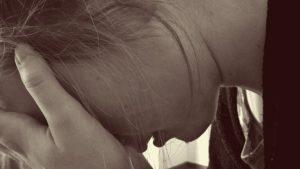 顔を隠しうつむく少女