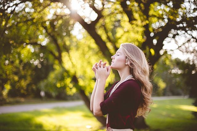 自然の中で目を閉じ祈る女性
